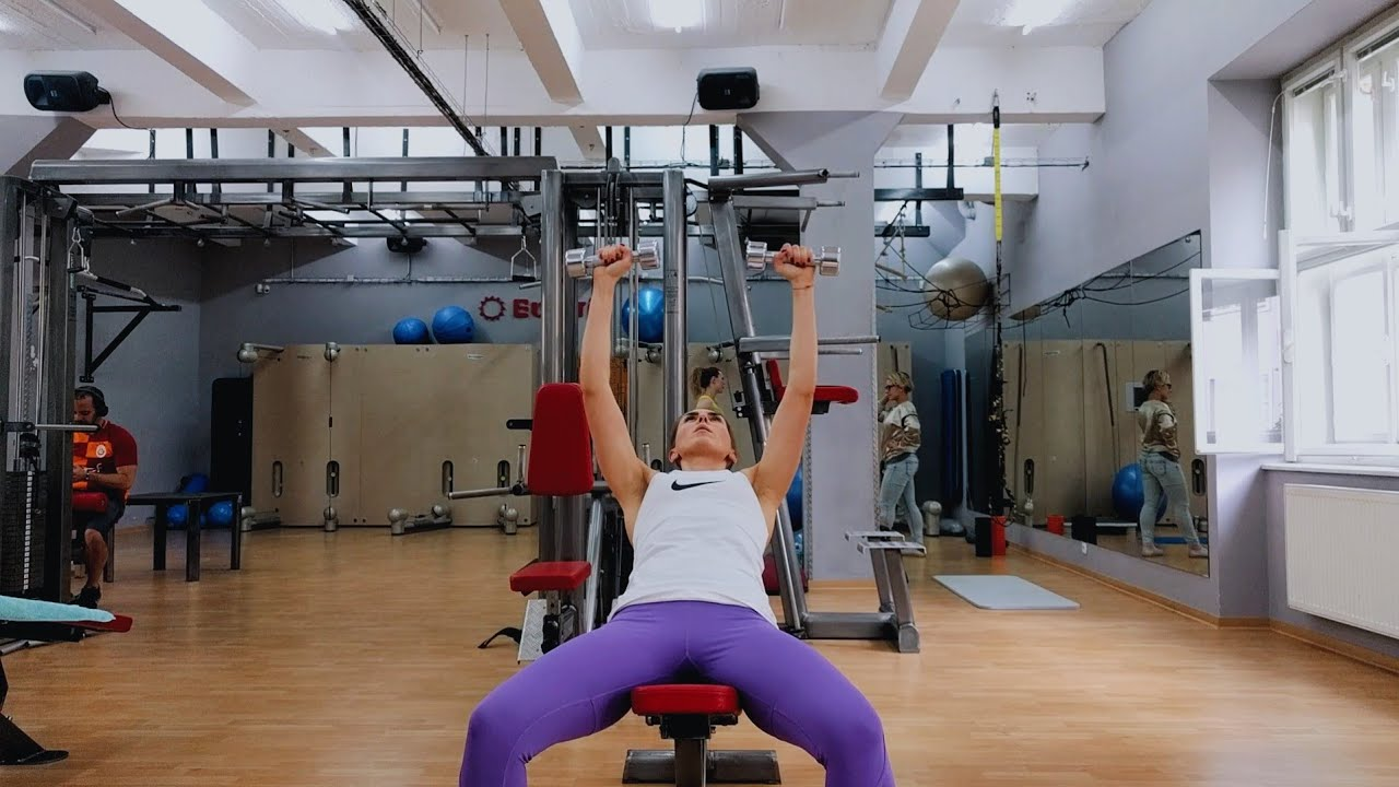Упражнение девушка выполняет упражнение жим гантелей лежа на наклонной скамье