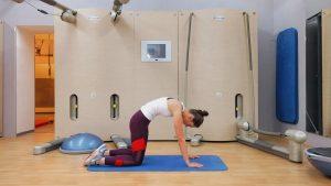 девушка выполняет упражнение для растяжки спины