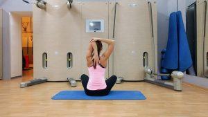 девушка выполняет упражнение на растяжку трицепса сидя на полу
