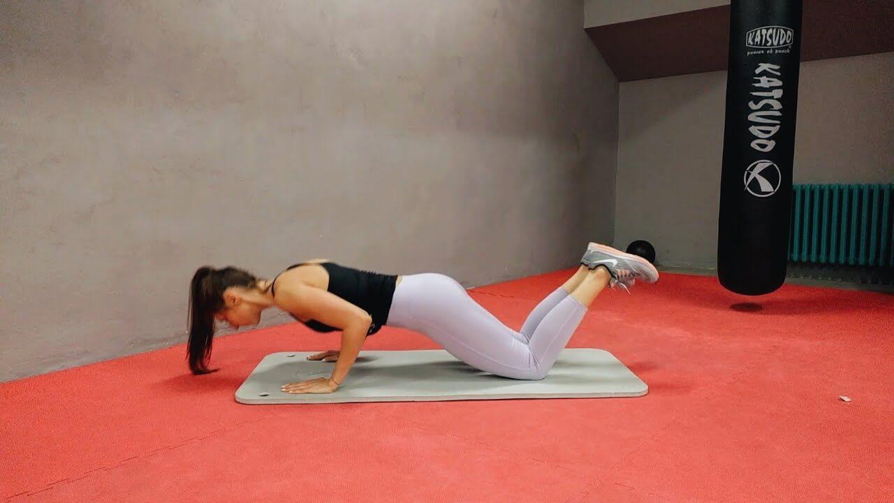 Девушка выполняет упражнение отжимания с колен с узкой постановкой рук