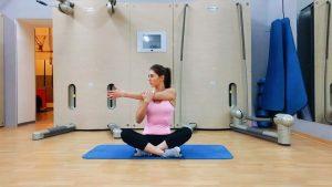 девушка выполняет упражнение для растяжки плеч сидя