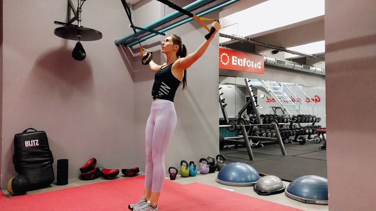 Упражнение девушка выполняет упражнение разведение рук в петлях TRX