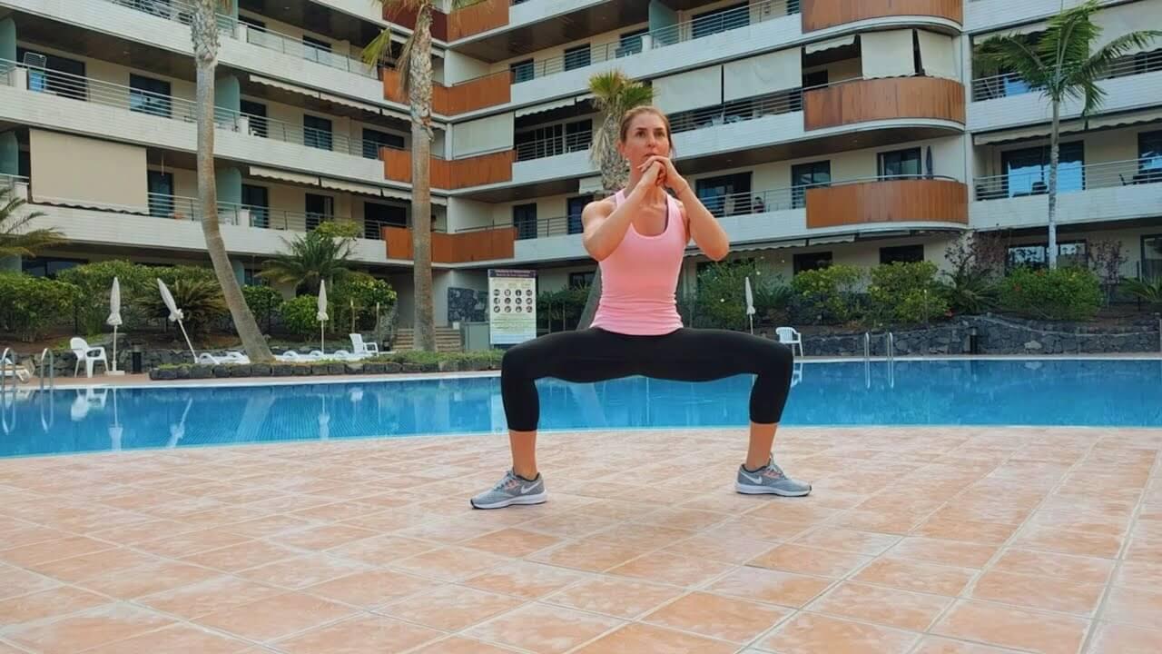 Упражнение девушка выполняет статические приседания-плие