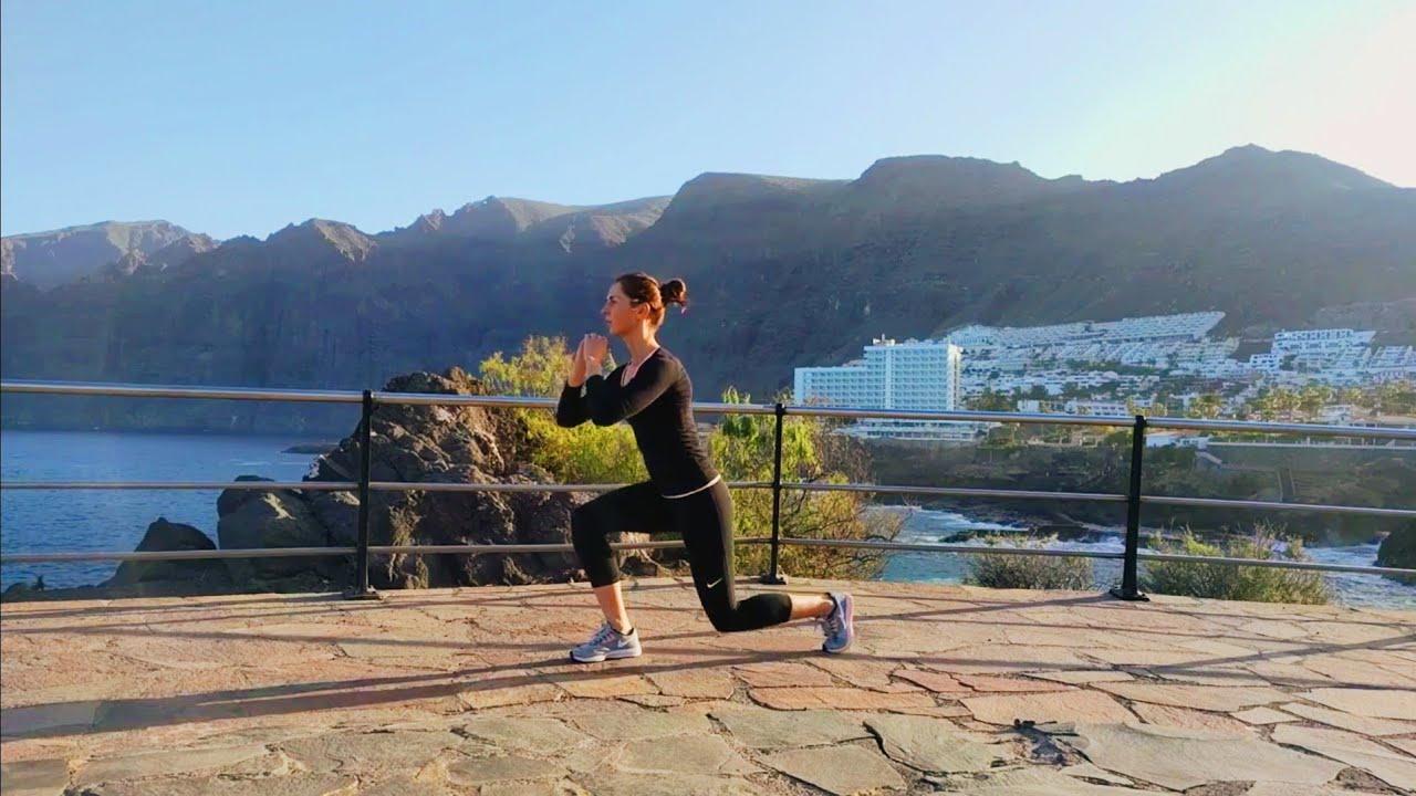 Упражнение девушка выполняет упражнение выпады назад с подтягиванием колена к груди