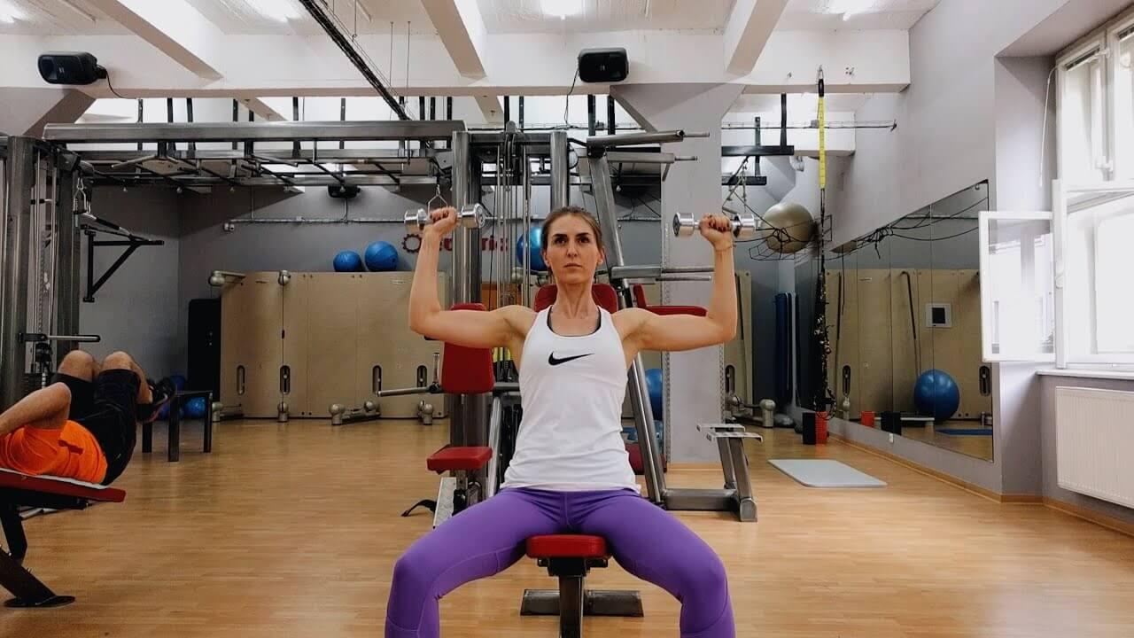 Упражнение Девушка выполняет упражнение жим гантелей на плечи сидя на скамье