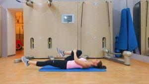 девушка выполняет упражнение на растяжку бицепса бедра лежа