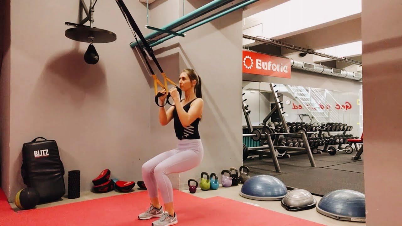Упражнение девушка выполняет приседания на ягодицы в петлях TRX