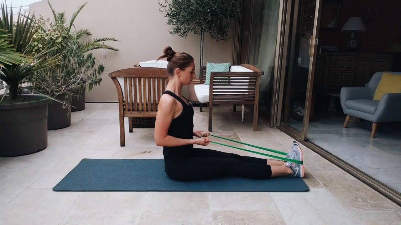 девушка выполняет упражнение тяга эластичной ленты к поясу сидя